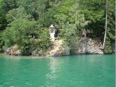Ein verträumter Winkel mit einem Marterl am See. Hier sieht man die tiefgrüne Farbe des Wassers sehr deutlich.