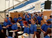 """Blaue T-Shirts überall. Der """"Stress"""" um die Mittagszeit ist oft groß. Die Gerichte müssen schnell zubereitet werden und die Bedienungen warten schon mit dem nächsten Zettel. Auch wenn diese Momentaufnahme etwas chaotisch wirkt, so ist hier ein eingespieltes Team am Werk, in dem jede/r seine Aufgabe hat."""
