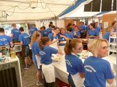 Viele blaue T-Shirts wuseln durch die Küche. Jede/r hat seine Aufgaben und weiß, was zu tun ist. Anders würden wir die Aufgaben nicht bewältigen können. Schön, dass Gitte und Elfriede da noch Zeit zum Scherzen haben.